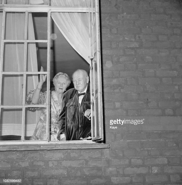 Sir Winston Churchill and his wife Clementine Churchill pictured together standing at an open window of their house in Kensington London on 10th...