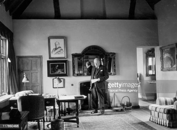 Sir Winston Churchill British politician and First Lord of the Admiralty standing by a mirror reading a document in the study of his country home...