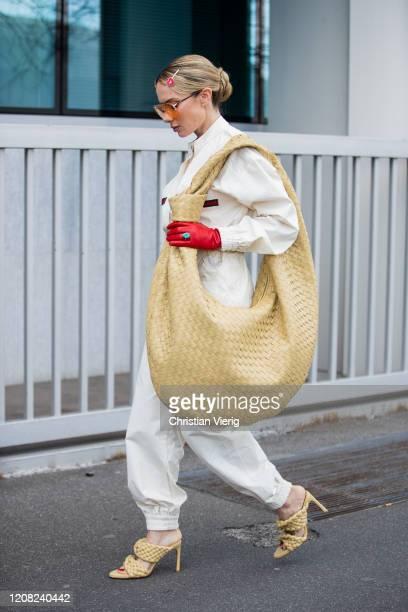 Sira Pevida is seen wearing beige oversized Bottega Veneta bag, sandals, Gucci overall, sunglasses, red gloves, Prada hair clip outside Boss during...