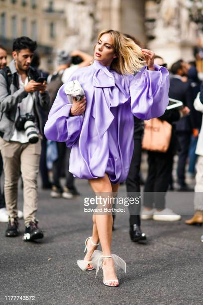 Sira Pevida wears a long sleeves puffy mauve mini dress, a cream-color bag, white heeled sandals with white tulle bows, outside Balmain, during Paris...