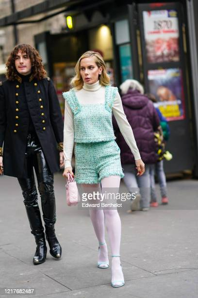Sira Pevida wears earrings, a white turtleneck, a fringed sea-green tweed top with large straps and bejeweled buttons, matched shorts, light pink...
