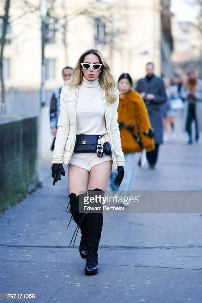Sira Pevida wears earrings, white sunglasses, a white turtleneck, a white jacket with a gold chain edging, white fluffy mini shorts, black leather...