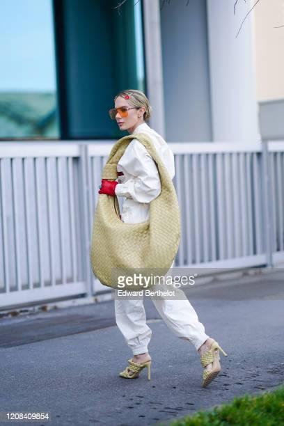 Sira Pevida wears orange glasses a large oversized Bottega Veneta bag a white jumpsuit quilted shoes outside BOSS during Milan Fashion Week...