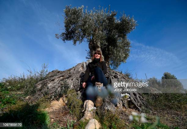 Sira Plana cofounder of Adopt an Olive Tree poses next to one in Oliete northeastern Spain on December 17 2018 Residents began moving away from rural...
