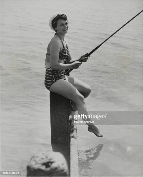 Siren Turns Her Charms On Fish, Perched on a breakwater, looking as tempting as the sirens of old, 17-year-old Miss Penny Gurd of Southend, turns her...