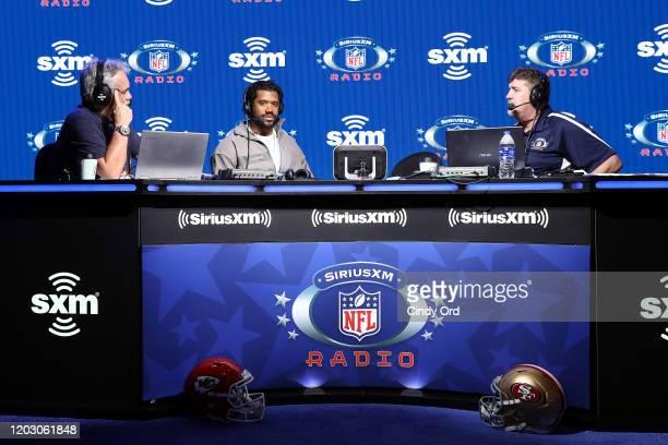 SiriusXM host Pat Kirwan NFL quarterback Russell Wilson of the Seattle Seahawks and SiriusXM host Jim Miller speak onstage during day 2 of SiriusXM...