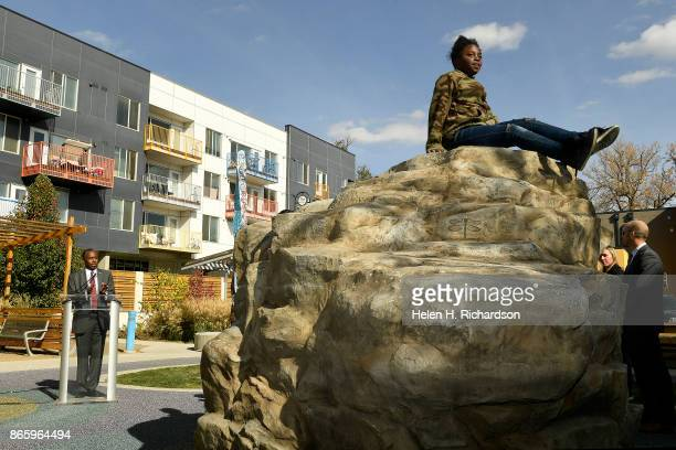 DENVER CO OCTOBER 23 Siriya Salonis right plays on a rock formation in the playground area as HUD Secretary Ben Carson speaks to members of the press...