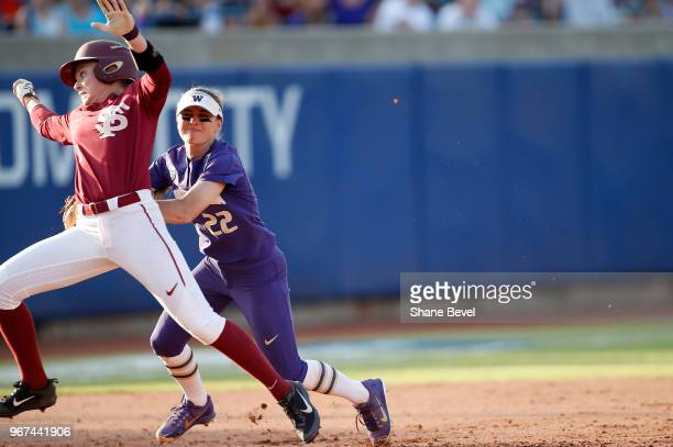 Sis Bates of the Washington Huskies tags out Dani Morgan of the Florida State Seminoles during the Division I Women's Softball Championship held at...