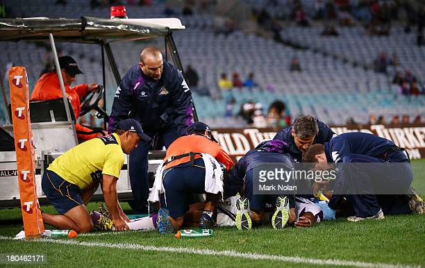 Sisa Waqa of the Storm receives medical attention after landing on his head after a mid air incident with Dylan Farrell of the Rabbitohs during the...