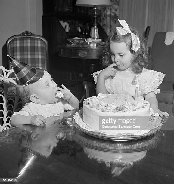 Sister and baby brother eating birthday cake
