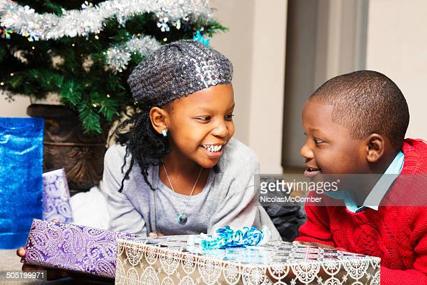 sister and brother anticipating their christmas presents - florida christmas stock pictures, royalty-free photos & images