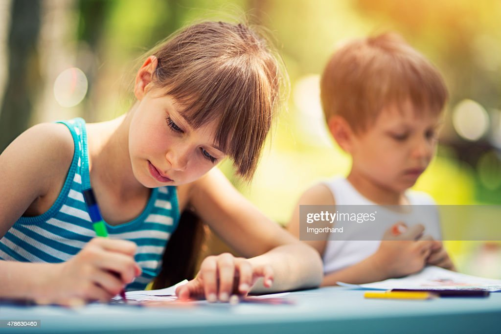Sister and brother drawing together outdoows : Stock Photo