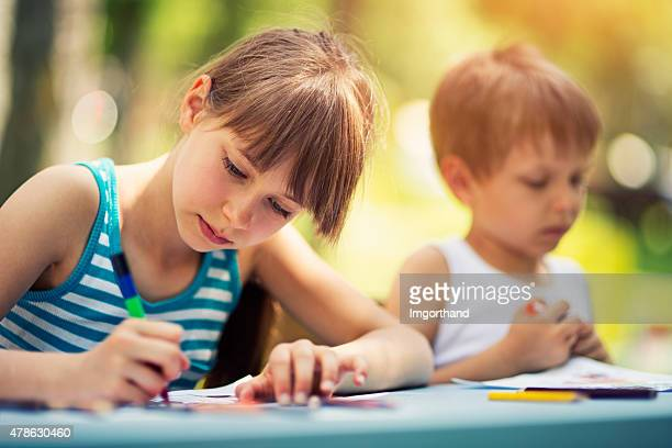 sister and brother drawing together outdoows - colouring stock photos and pictures