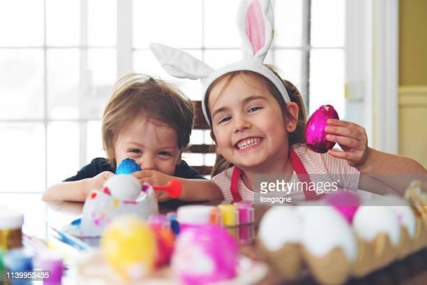 irmã e irmão que comem o chocolate - easter - fotografias e filmes do acervo