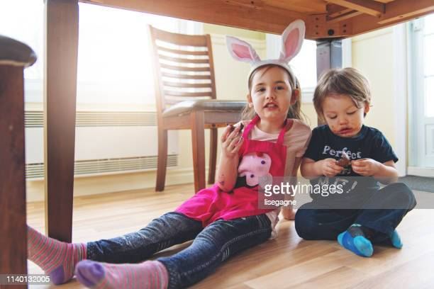 sister and brother eating chocolate - dirty easter stock pictures, royalty-free photos & images