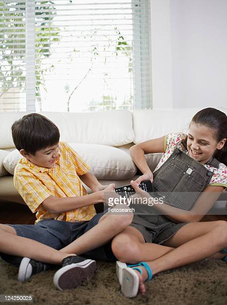 sister and brother fighting over remote control - brother stock pictures, royalty-free photos & images