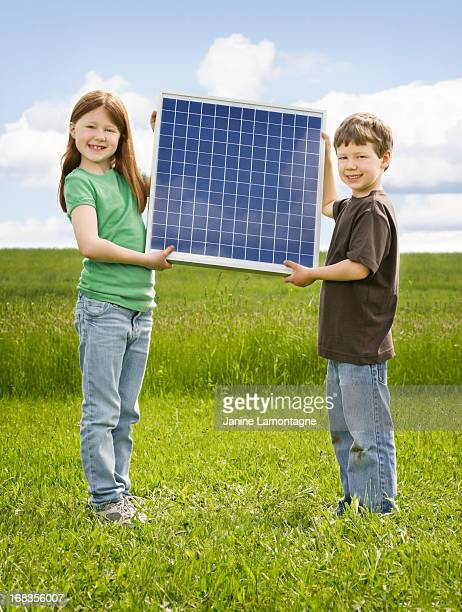 sister and brother hold solar panel - solar mirror stock pictures, royalty-free photos & images
