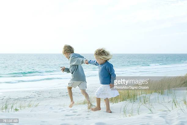 sister and brother holding hands on beach - unrecognisable person stock pictures, royalty-free photos & images