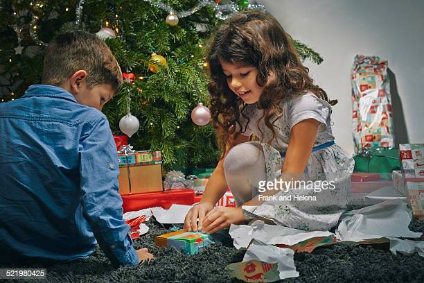 Sister and brother in sitting room unwrapping christmas gifts