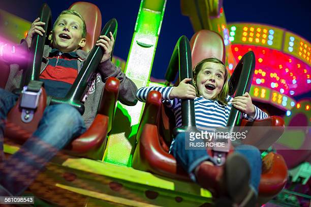 Sister and brother on fairground ride at night