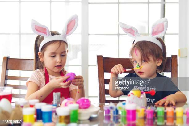 sister and brother painting easter eggs - dirty easter stock pictures, royalty-free photos & images