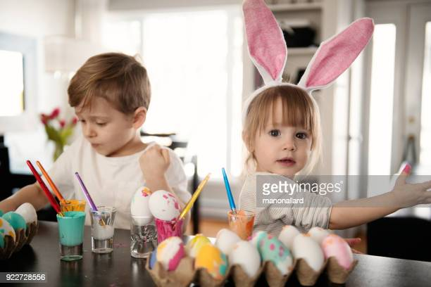 sister and brother painting easter eggs. - pasqua foto e immagini stock