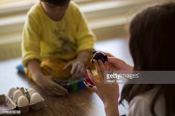 sister and brother painting eggs - dirty easter stock pictures, royalty-free photos & images
