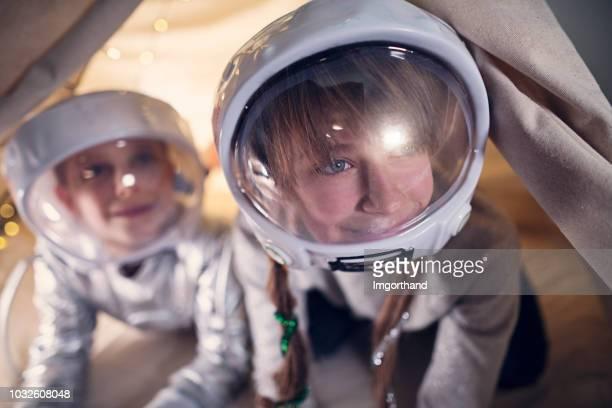 hermana y hermano jugar a astronautas en su habitación - traje espacial fotografías e imágenes de stock