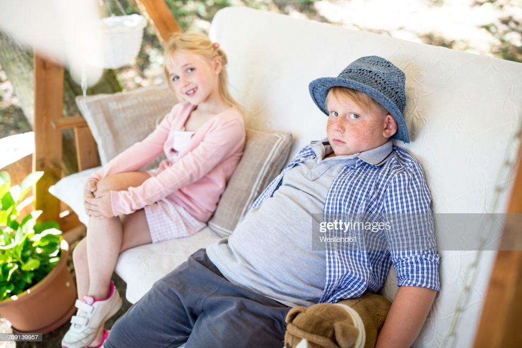 Sister and brother sitting in canopy swing : Stock Photo