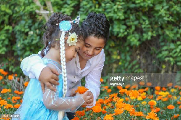 Sister and brother smelling flower in garden