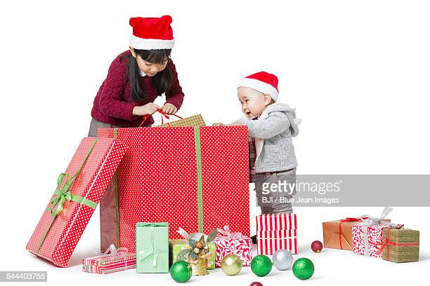 Sister and brother unwrapping Christmas gift