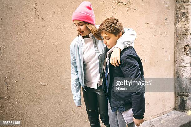 sister and brother walking through street - petite teen girl stock photos and pictures