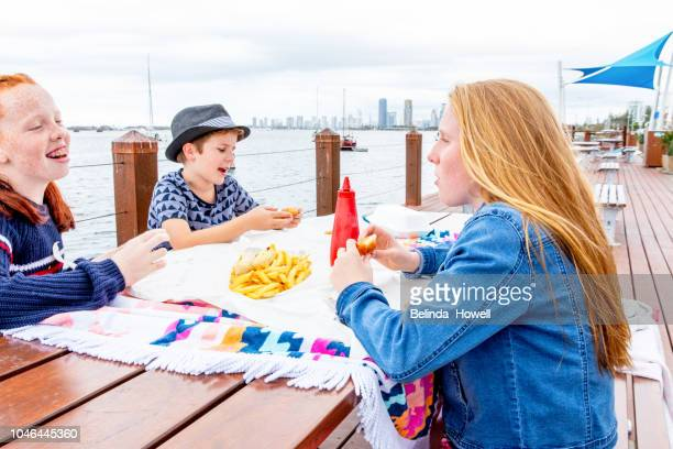 Sister and brother with a friend share fish and chips for lunch by the water