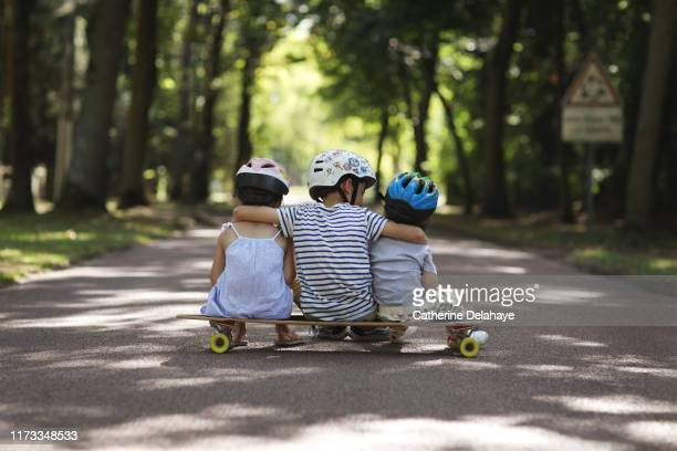 3 sister and brothers sitting on a skateboard in the street - seulement des enfants photos et images de collection