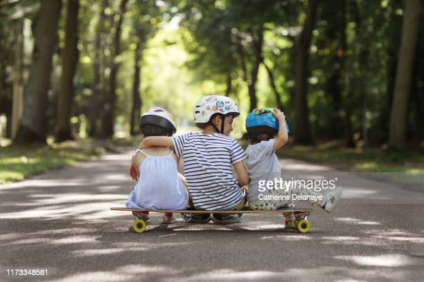 3 sister and brothers sitting on a skateboard in the street - sister stock pictures, royalty-free photos & images