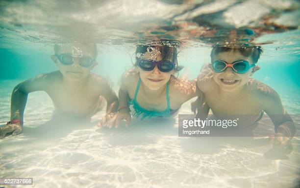 Sister and brothers swimming underwater in shallow pool