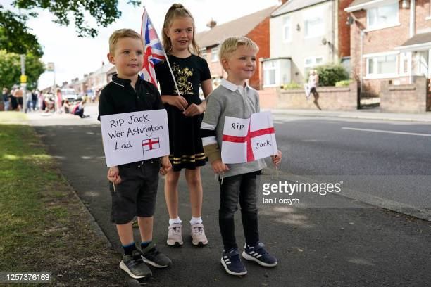 Sister and her brothers hold homemade signs as they join well wishers on the streets of Ashington in Northumberland to pay their respects as the...