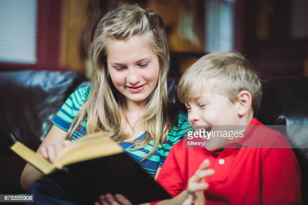 sister and younger brother haviong fun reading a book - storyteller stock pictures, royalty-free photos & images