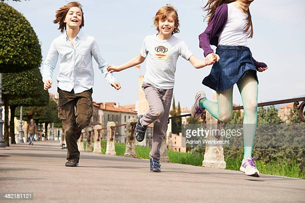 Sister and younger brothers running through park, Province of Venice, Italy