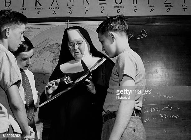 Sister Aquinas the flying nun in their classroom at Catholic university looking over a student's model plane Washington DC June 1943
