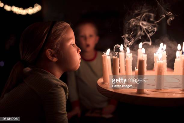 sister blowing candles on table during christmas with brother in background at home - christmas decore candle stock pictures, royalty-free photos & images