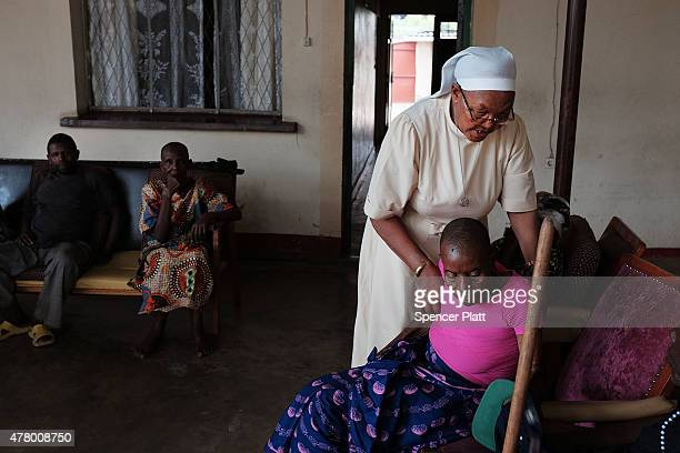 Sister Colette Murimbane helps a patient in the Christian medical clinic Saint Elizabeth Auberge on June 21, 2015 in Bujumbura, Burundi. The clinic...