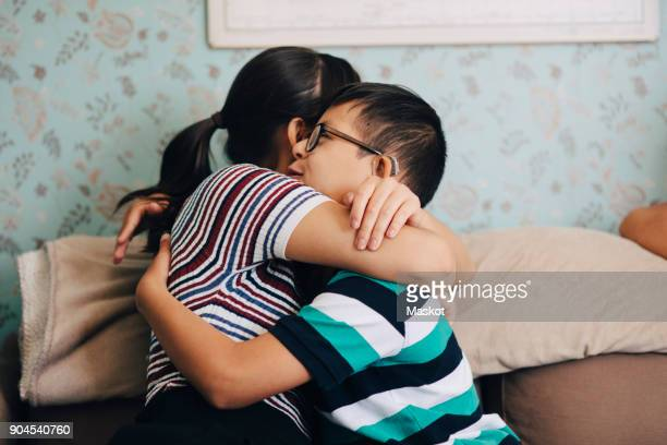 Sister embracing boy while sitting on sofa against wall at home