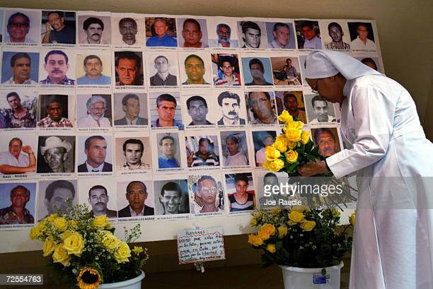 Sister Eugracia gathers flowers in front of photographs of arrested dissidents May 13 2004 in Miami Florida Cuban Americans came together to show...