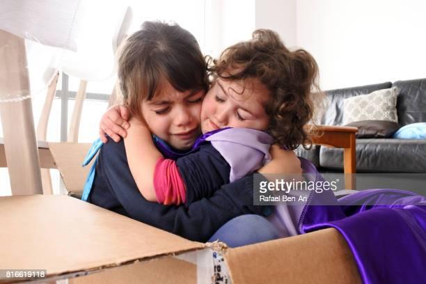sister girls hugging each other after a fight - rafael ben ari stock-fotos und bilder