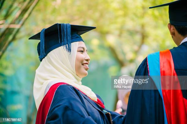 sister helping brother with his graduation gown - rifka hayati stock pictures, royalty-free photos & images