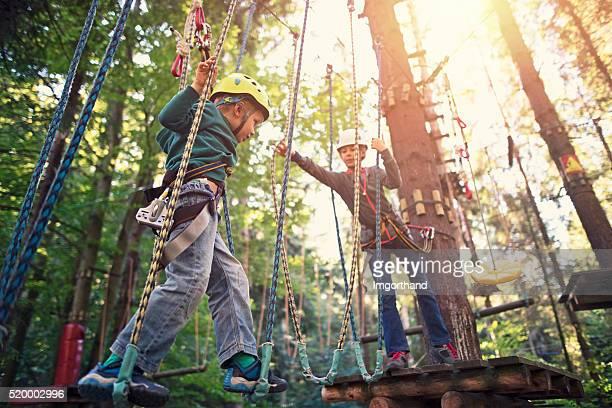 Schwester helfen, ihr Bruder während Seile Kurs in Abenteuer Park