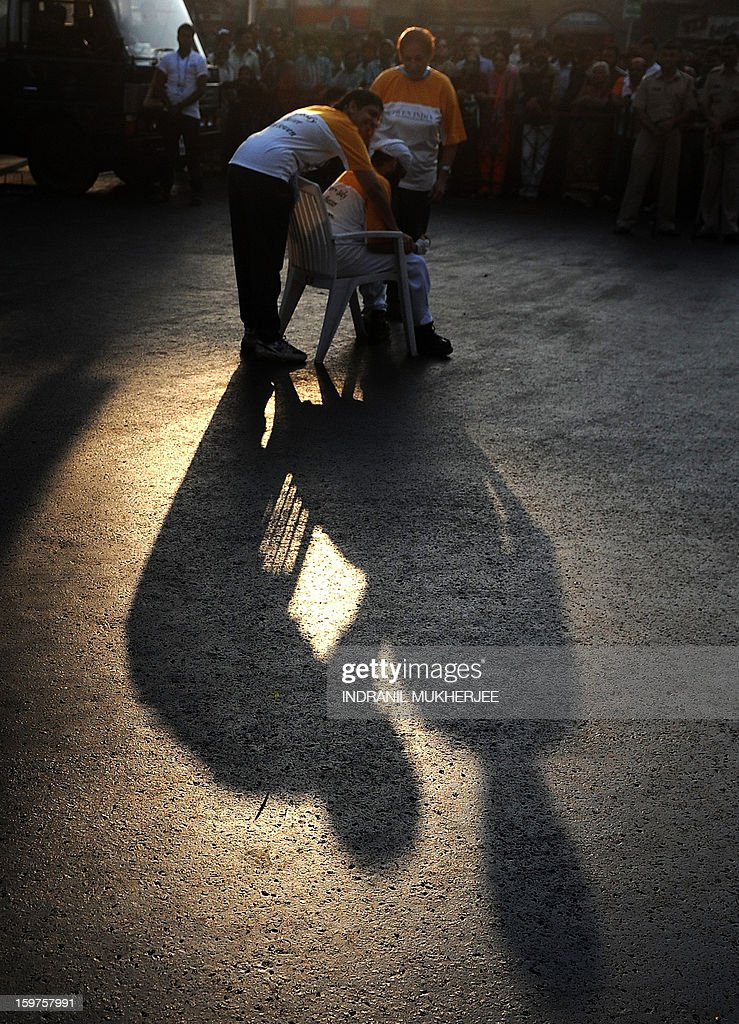 A sister (L) helps her paraplegic brother with a chair to take rest after every few steps as they take part in the Mumbai Marathon on January 20, 2013. Thousands of people turned out on a cool morning to take part in the annual race in the Indian city. AFP PHOTO/Indranil MUKHERJEE