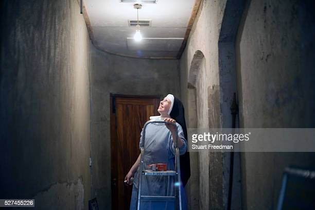 Sister Katherine changes a lighbulb at Tyburn Convent London UK Tyburn near Marble Arch was the site of ' The King's Gallows' from 1196 to 1783 It...