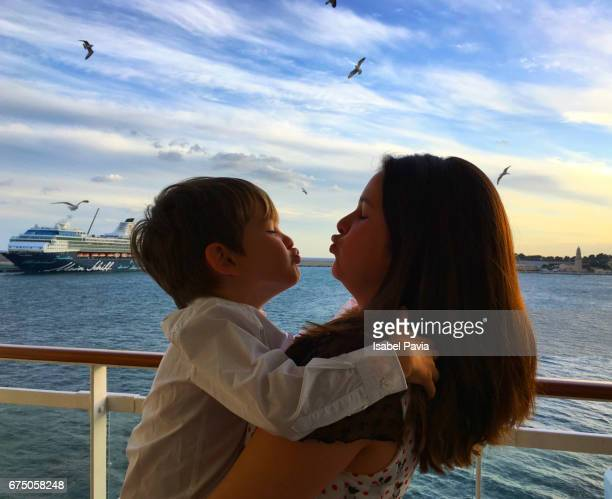 sister kissing brother at sunset on a cruise ship - paquebot france photos et images de collection